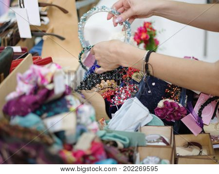 Close-up picture of a fashionable female choosing hair accessories on a blurred fancy shop background. Sparkly bracelets, cute hair hoops, colorful barrettes and pretty hair clips on store shelves.