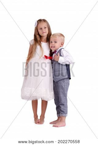 A pretty girl in a fancy dress and a boy in a classy suit standing next to each other. A pair of little siblings isolated over the white background. Childhood, family concept.