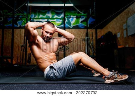 A photo of a beautiful bodybuilder doing a physical exercise on a colorful gym background. A sexual and attractive man pumping up his muscles on a floor. Fitness, sports, healthy concept. Copy space.