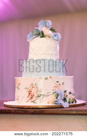party treatment sweet life concept. on the flat dish there is marvelous three-tiered birthday cake made of white and blue cream and decorated with various flowers