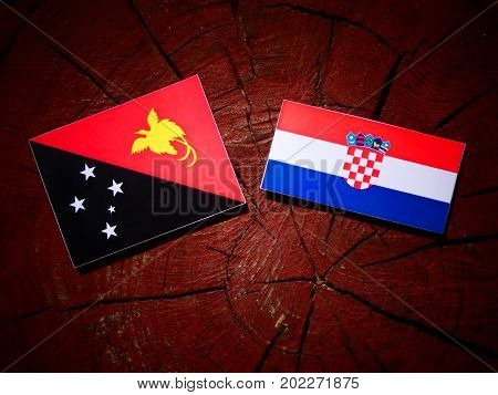 Papua New Guinea Flag With Croatian Flag On A Tree Stump Isolated