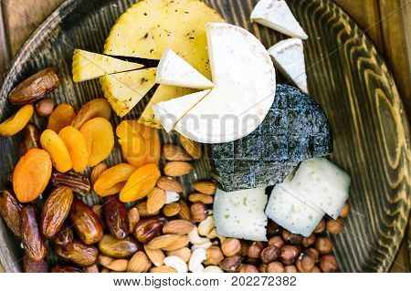 meal, setting, lifestyle concept. close up of delicious and healthy products represented by few types and coloures cheese heads, surrounded by snakes such as two kinds of dried fruits and nuts