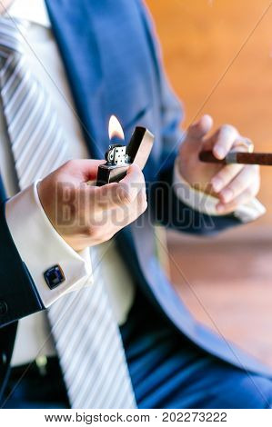 success, smoking, celebration concept. well groomed arms of caucasian man, dressed in blue fashion costume made to measure with marvelous cufflinks, taking lightner and cheroot