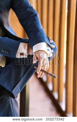 virility, solvency, business concept. close up of arms of young wealthy man wearing blue tweed suit with wondreful cufflinks, crossing his legs and smoking cigar