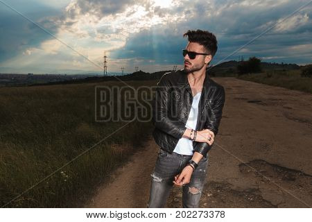 man in leather jacket and  sunglasses holds his elbow while standing to a side of a country road
