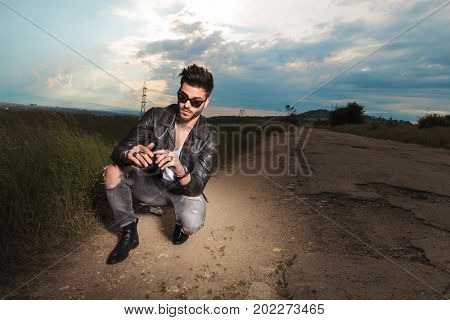 cool gouy smoking on a country road in the middle of nowhere