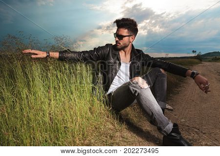 seated man in leather jacket touching the tall grass while smoking a cigarette on the side of the road