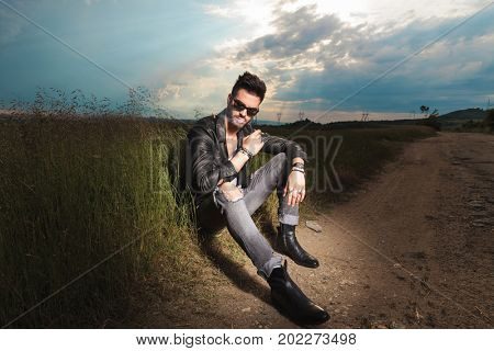 man in leather jacket sits on the side of a country road and enjoys his cigarette