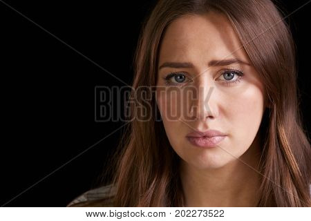 Close Up Head And Shoulders Studio Portrait Of Anxious Woman