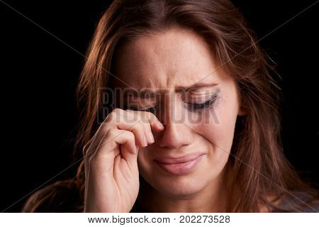Studio Shot Of Crying Young Woman With Smudged Eye Make Up