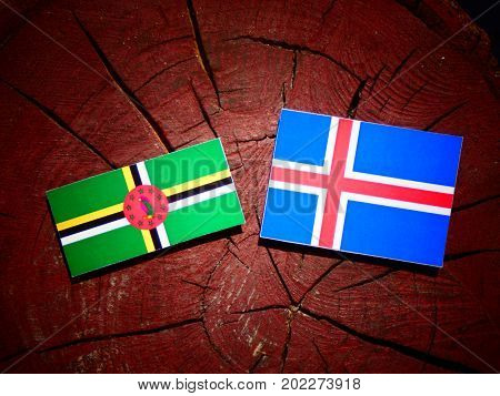 Dominica Flag With Icelandic Flag On A Tree Stump Isolated