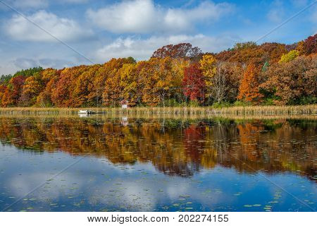 a calm windless autumn day reflects a variety of colors on east boot lake washington county minnesota.