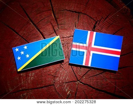 Solomon Islands Flag With Icelandic Flag On A Tree Stump Isolated