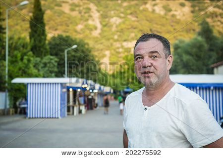 Middle-aged unshaven man in a T-shirt outdoor portrait
