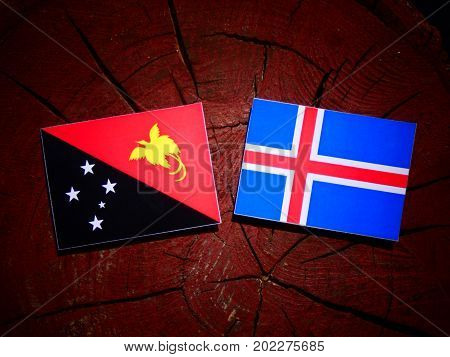 Papua New Guinea Flag With Icelandic Flag On A Tree Stump Isolated