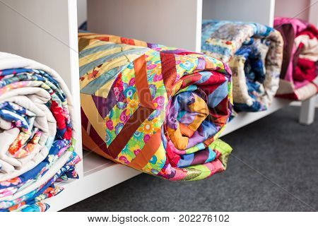 patchwork, sewing and fashion concept - some colorful finished quilted blanket in the studio at white shelves with few storage compartments, the warehouse of finished products, side view