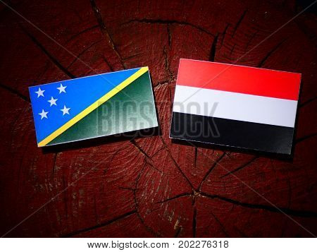 Solomon Islands Flag With Yemeni Flag On A Tree Stump Isolated