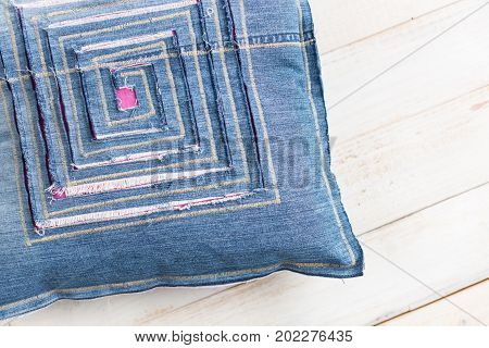 textile blue pillow on a white background, close up on the pillow decorated with stitching and designer decor in the form of labyrinth cut in fabric through which visible colored lining, top view
