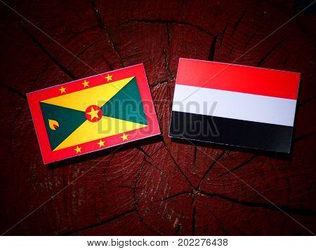 Grenada Flag With Yemeni Flag On A Tree Stump Isolated