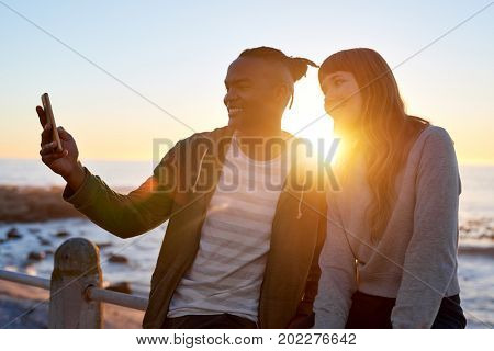 Multi racial friends couple smiling for cellphone selfie outdoors at sunset by ocean
