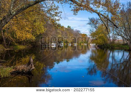 pontoon boats line the backwater banks of the st.croix river in autumn in the village of marine on the st. croix minnesota.