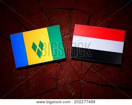 Saint Vincent And The Grenadines Flag With Yemeni Flag On A Tree Stump Isolated