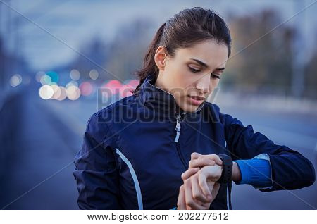 Young woman checking time after run in street. Athletic girl ready to run and looking at sport smart watch. Healthy runner checking performance or heart rate at dusk in the city.