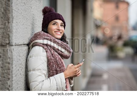 Pensive young woman holding smartphone and looking up. Happy smiling woman in winter with cap and woolen scarf thinking about the future. Latin girl standing on the street and looking away.