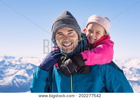Young daughter riding piggyback on her father's shoulder. Father and daughter enjoying snow during winter vacation. Portrait of happy man and cute girl have fun in snow mountains.