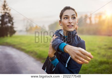 Woman stretching at park while listening to music. Young woman working out at sunset. Healthy sport girl doing stretching exercise early in the morning at park.
