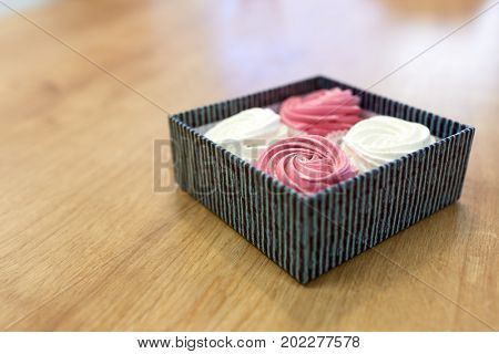 food, confection and sweets concept - zephyr, marshmallow or whipped cream in gift box on wooden table