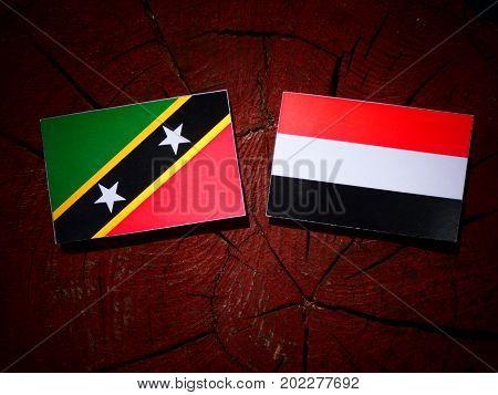 Saint Kitts And Nevis Flag With Yemeni Flag On A Tree Stump Isolated