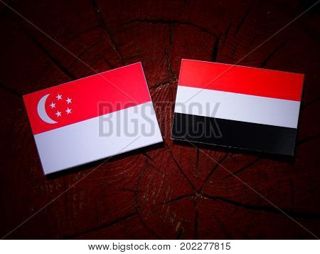 Singaporean Flag With Yemeni Flag On A Tree Stump Isolated