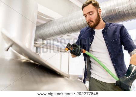 alcohol production, business and people concept - man with hose working at craft beer brewery kettle