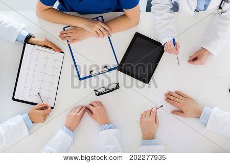 medicine, healthcare and cardiology concept - group of doctors with cardiogram, clipboard and tablet pc computer at hospital