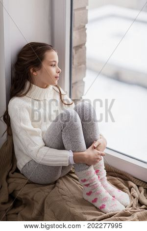 childhood, sadness and people concept - sad beautiful girl in sweater sitting on sill at home window in winter