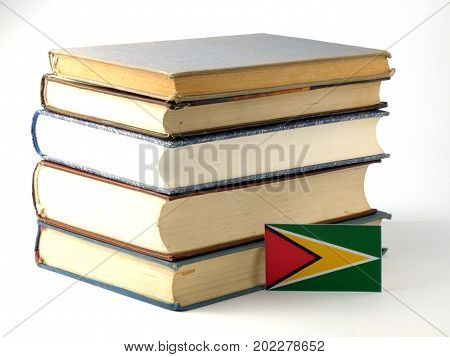 Guyana Flag With Pile Of Books Isolated On White Background