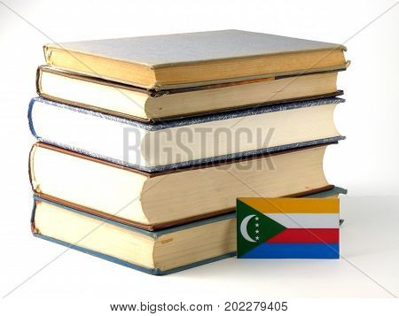 Comoros Flag With Pile Of Books Isolated On White Background