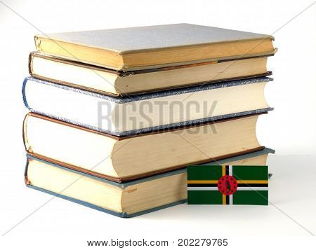 Dominica Flag With Pile Of Books Isolated On White Background