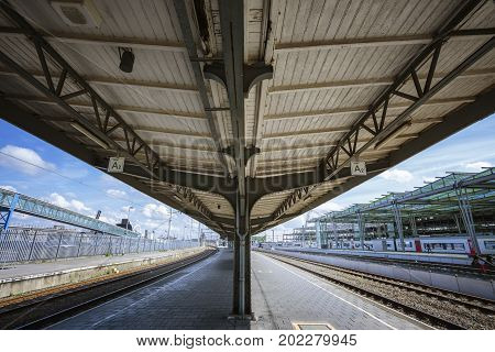 OOSTENDE BELGIUM - JUNE 22 2016: Wide upward picture of a platform inside Oostende railway station with no people in a sunny day with clouds