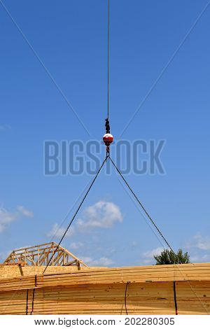 A boom and cable transfer a load of pre-made rafters(trusses) to the top of a building under construction.