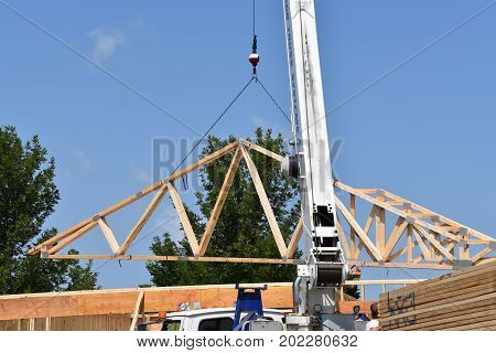 A crane, boom, and cable transfer a load of pre-made rafters(trusses) to the top of a building under construction.
