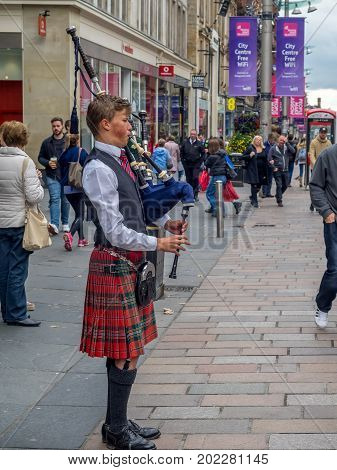 GLASGOW, SCOTLAND - JULY 21: A bagpiper on Buchanan Street on July 21, 2017 in Glasgow, Scotland. Buchanan Street is a popular tourist destination and so there is always a bagpiper busking for change.