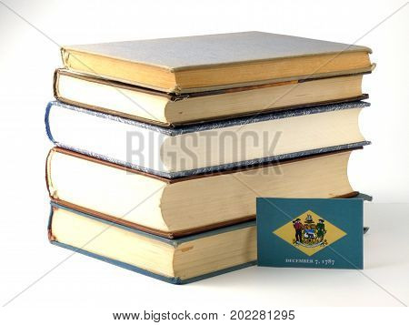 Delaware Flag With Pile Of Books Isolated On White Background