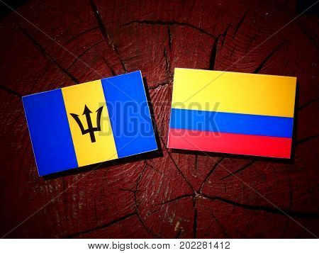 Barbados Flag With Colombian Flag On A Tree Stump Isolated