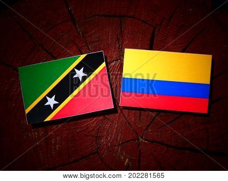 Saint Kitts And Nevis Flag With Colombian Flag On A Tree Stump Isolated