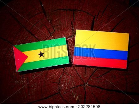 Sao Tome And Principe Flag With Colombian Flag On A Tree Stump Isolated