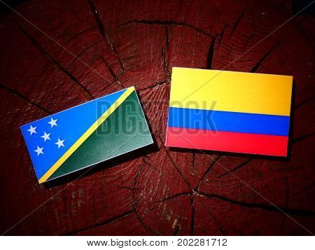 Solomon Islands Flag With Colombian Flag On A Tree Stump Isolated