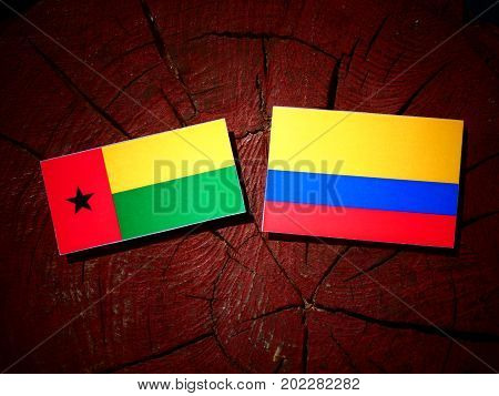 Guinea Bissau Flag With Colombian Flag On A Tree Stump Isolated