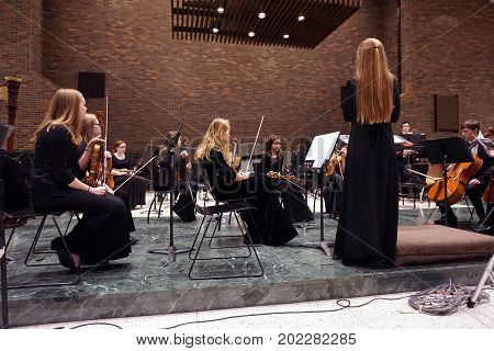 ROMEOVILLE, ILLINOIS / UNITED STATES - OCTOBER 26, 2016: The concert mistress of the Metropolitan Youth Symphony Orchestra (MYSO) stands before the orchestra members, to direct the tuning of instruments, prior to a concert at Lewis University.